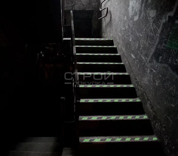 Клеющаяся светящаяся лента на темной лестнице в подвале.