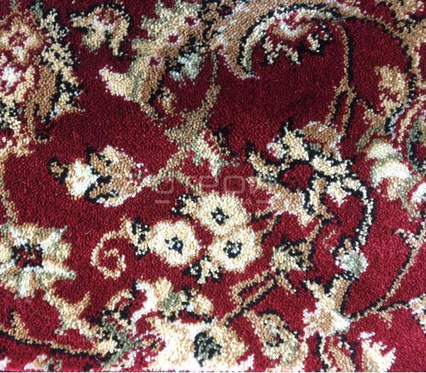 Фактура ковролина бордового коврика на домашнюю деревянную лестницу.