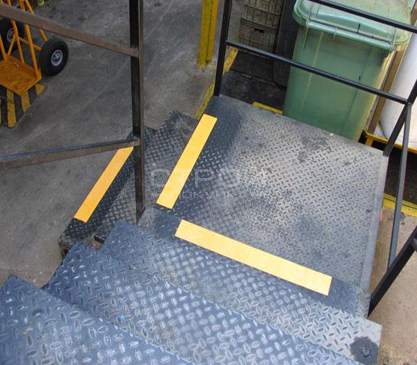 Желтая алюминиевая клейкая лента 50 мм на металлической лестнице