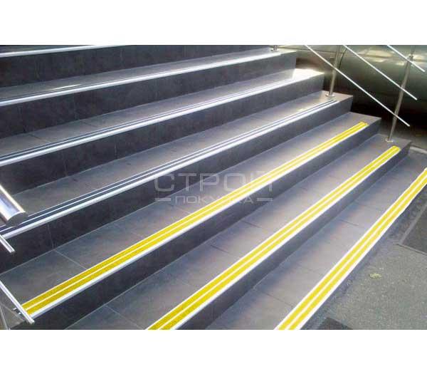 Установленный на лестницу алюминиевый угол порог с двумя цветными резиновыми вставками.