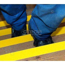 Желтая противоскользящая лента на деревянной лестнице