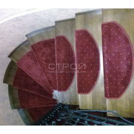 Красные накладки на ступеньки на деревянной лестнице.
