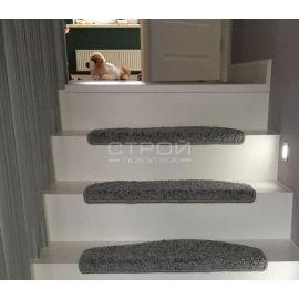 Загиб коврика Венеция серого на белых ступенях.