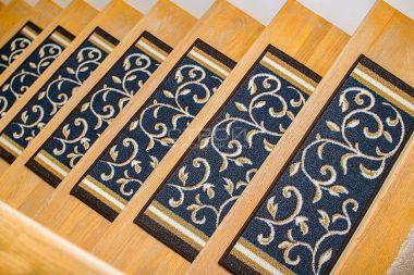 Прямоугольные коврики на ступени лестницы из светлого дерева.