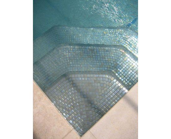 Глянцевая мозаика Inox Metal серого цвета производства Ezarri переливается на солнечном свете.